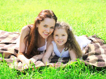 Happy mother and child with toothy smiles lying resting Royalty Free Stock Photography