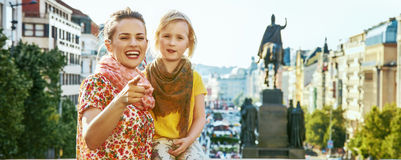 Happy mother and child tourists in Prague pointing in camera Imagen de archivo