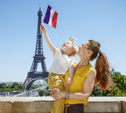 Happy mother and child tourists rising flag in Paris, France Stock Image