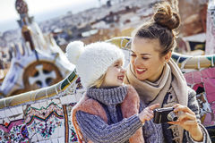 Happy mother and child viewing photos on camera at Guell Park Royalty Free Stock Images