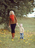 Happy mother and child walking together in the autumn Stock Photos