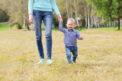 Happy mother and child walking together outdoors Stock Images