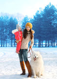 Happy mother and child walking with white Samoyed dog in winter Stock Photography