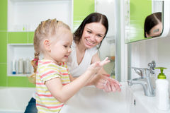 Happy mother and child washing hands with soap in. Happy mother and child washing hands with soap together in bathroom stock images