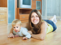 Happy mother and child on wooden floor Stock Images