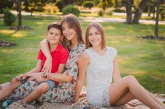 A happy mother and children are having fun in the park on a warm summer day. They`re on the lawn in the park. A happy mother and children are having fun in the royalty free stock photo