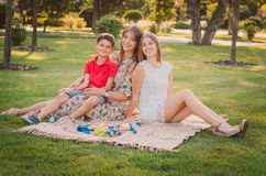 A happy mother and children are having fun in the park on a warm summer day. They`re on the lawn in the park. A happy mother and children are having fun in the stock image