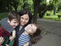 Happy mother and children. A happy mother and her children laughing in a park stock images