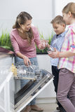 Happy mother and children placing glasses in dishwasher Royalty Free Stock Photos