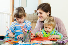 Happy mother and children sketching with pencils Stock Photo