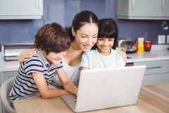 Happy mother and children working on laptop Royalty Free Stock Images