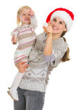 Happy mother in Christmas hat holding baby girl Royalty Free Stock Image