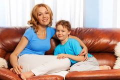 Happy mother cuddles son on couch Stock Images
