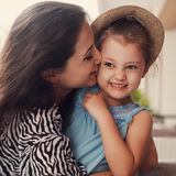Happy mother cuddling and kissing her cute kid girl in hat. Tone Royalty Free Stock Photo