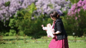 Happy mother and cute baby-girl playing together in a park against flowers. stock footage