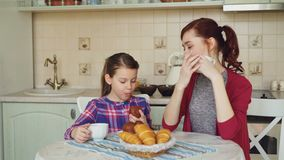 Happy mother and cute daughter having breakfast eating muffins and talking at home in modern kitchen. Family, food, home stock video