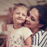 Happy mother and cute enjoying girl cuddling with love indoor. C Stock Photo