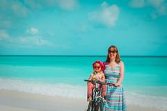 Happy mother with cute little baby girl bike at beach. Vacation royalty free stock photos