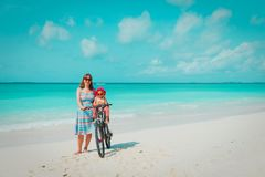 Happy mother with cute little baby girl bike at beach royalty free stock photography