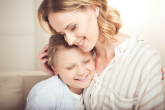 Happy mother and cute little son hugging together at home. Close-up portrait of happy mother and cute little son hugging together at home royalty free stock photography