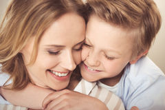 Happy mother and cute little son hugging together at home. Close-up portrait of happy mother and cute little son hugging together at home stock image