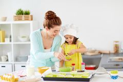 Happy mother and daughter baking cupcakes at home Stock Photo