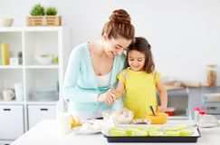 Happy mother and daughter baking muffins at home. Family, cooking, baking and people concept - happy mother and little daughter making batter for muffins at home stock photography