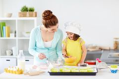 Happy mother and daughter baking muffins at home. Family, cooking, baking and people concept - happy mother and little daughter making batter for muffins at home royalty free stock photos