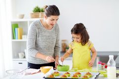 Happy mother and daughter baking muffins at home. Family, cooking, baking and people concept - happy mother and little daughter making batter for muffins at home royalty free stock photography