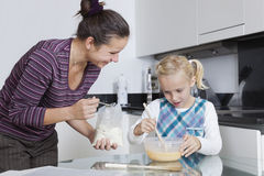 Happy mother and daughter baking together in kitchen Royalty Free Stock Photo