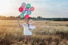 Happy mother and daughter with balloons at sunset Royalty Free Stock Images
