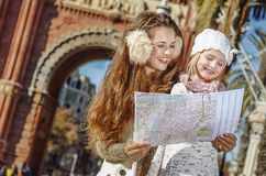 Happy mother and daughter in Barcelona, Spain looking at map Stock Images