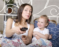 Happy mother with daughter in bed watching tv Royalty Free Stock Photos