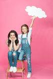 Happy mother and daughter with blank speech bubble posing on stool Royalty Free Stock Image