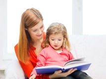 Happy mother and daughter with book Stock Photo