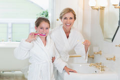 Happy mother and daughter brushing teeth together Royalty Free Stock Images