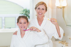 Happy mother and daughter brushing teeth together Stock Photo