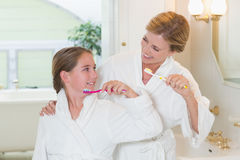 Happy mother and daughter brushing teeth together Royalty Free Stock Image
