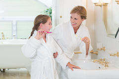 Happy mother and daughter brushing teeth together royalty free stock photos