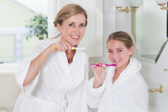 Happy mother and daughter brushing teeth together Stock Image