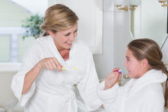 Happy mother and daughter brushing teeth together Stock Images