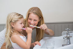 Happy mother and daughter brushing their teeth Stock Image