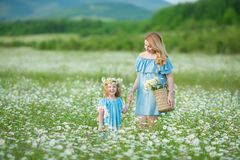 Happy mother and daughter child together with yellow dandelion flowers in summer day enjoy vacation free time together happy stock photography