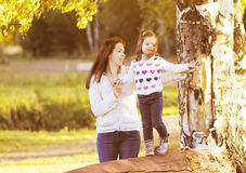 Happy mother and daughter child walking in sunny autumn Royalty Free Stock Photos