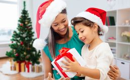 Happy mother and daughter with christmas gift. Holidays, family and people concept - happy mother and daughter with christmas gift stock photos