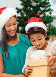 Happy mother and daughter with christmas gift. Holidays, family and people concept - happy mother and daughter with christmas gift royalty free stock photo