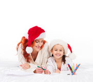 A happy mother and a daughter in Christmas hats Royalty Free Stock Image