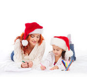 A happy mother and a daughter in Christmas hats Stock Photos