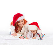 A happy mother and a daughter in Christmas hats Royalty Free Stock Photo