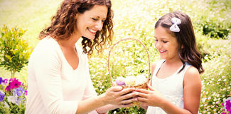 Happy mother and daughter collecting easter eggs. In the garden royalty free stock image